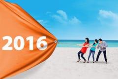 Povos que puxam a bandeira com números na praia Foto de Stock Royalty Free