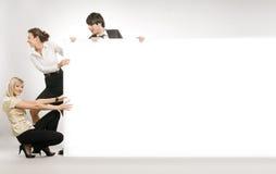 Povos que puxam a placa branca grande, Fotografia de Stock