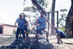 Povos que recebem o treinamento do curso de obstáculo do pneu imagens de stock royalty free