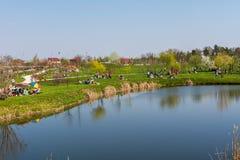 Povos que relaxam em um parque em um dia de mola ensolarado imagens de stock royalty free