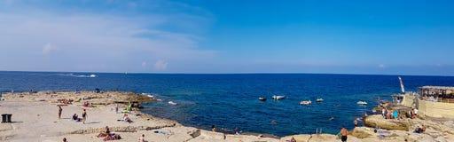 Povos que relaxam em uma praia em Malta imagem de stock royalty free