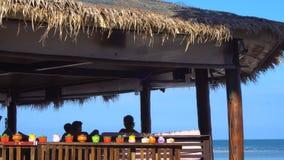Povos que relaxam na cabana de bambu pelo mar video estoque