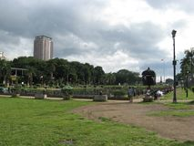 Povos que relaxam perto da lagoa central do parque de Rizal, Manila, Filipinas foto de stock