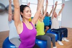 Povos que sentam-se em bolas do exercício com as mãos levantadas Foto de Stock Royalty Free