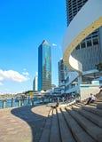 Povos que sentam-se em etapas perto de Eagle Street Pier com os raspadores do céu no fundo no CBD Brisbane Queensland Australi foto de stock
