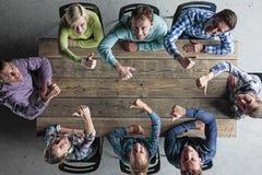 Povos que sentam-se em torno da tabela com polegares acima Foto de Stock Royalty Free