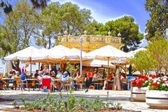 Povos que sentam-se junto nas tabelas e nas cadeiras que têm bebidas e alimento em um café exterior em um parque em Valletta Malt imagem de stock royalty free