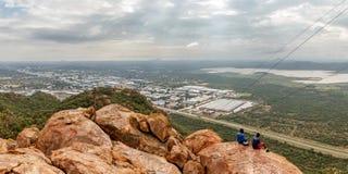 Povos que sentam-se nas pedras na montanha com cidade de Gaborone Fotos de Stock