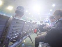 Povos que sentam-se no banco que espera seus voos no aeroporto Fotografia de Stock