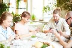 Povos que sentam-se no café e que olham o smartphone fotos de stock royalty free