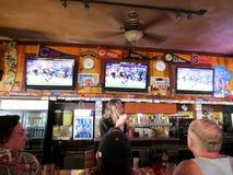 Povos que sentam-se no jogo de Superbowl do relógio da barra acima do barman no CI Foto de Stock Royalty Free