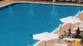 Povos que sentam-se pela piscina de uma piscina do recurso durante férias de verão video estoque