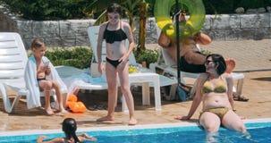 Povos que sentam-se pela piscina de uma piscina do recurso durante férias de verão filme