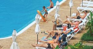 Povos que sentam-se pela piscina de uma piscina do recurso durante férias de verão vídeos de arquivo