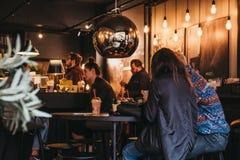 Povos que têm bebidas dentro de Joe e do café do suco em Hampstead, Londres, Reino Unido imagem de stock