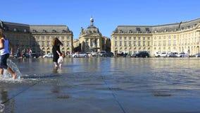 Povos que têm o divertimento em uma fonte do espelho na frente de Lugar de la a Bolsa no Bordéus, França filme