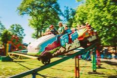 Povos que têm o divertimento no roller coaster no parque Imagem de Stock