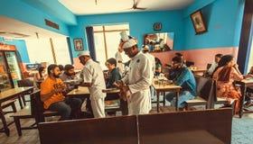 Povos que têm o jantar dentro do café indiano colorido com garçons ocupados Imagem de Stock Royalty Free