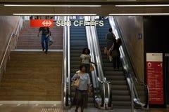 Povos que tomam as escadas rolantes do estação de caminhos-de-ferro Gare de Cornavin de Cornavin, logotipo do alimentador de form Fotos de Stock Royalty Free