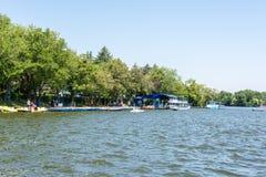 Povos que tomam o passeio da excursão do barco do cais do lago Fotos de Stock