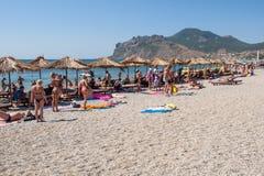Povos que tomam sol na praia Imagem de Stock