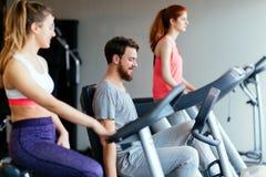 Povos que traning no gym em várias máquinas imagens de stock royalty free