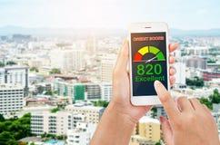 Povos que usam o smartphone sobre a pontua??o de cr?dito para bens imobili?rios da compra imagem de stock