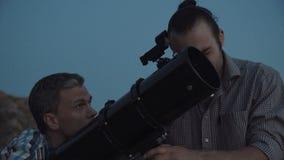 Povos que usam o telescópio no alvorecer vídeos de arquivo