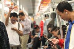 Povos que usam telefones no metro Imagens de Stock Royalty Free