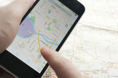Povos que verificam o smartphone com o mpa do navegador de GPS Imagens de Stock Royalty Free
