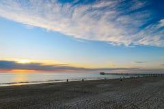Povos que wailking ao longo da praia no por do sol fotos de stock