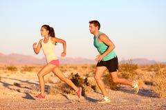 Povos running da fuga através dos campos no por do sol Fotografia de Stock