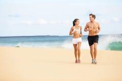 Povos running - pares dos corredores na corrida da praia Imagem de Stock