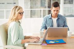 Povos sérios que trabalham no portátil ao sentar-se na mesa Foto de Stock Royalty Free