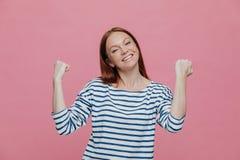 Povos, sucesso, realização e conceito da determinação A mulher bonita extático feliz levanta as mãos nos punhos, comemora sua vit fotos de stock