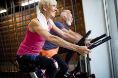 Povos superiores felizes que fazem biking interno em um clube de aptid?o foto de stock royalty free