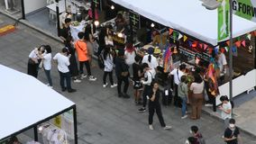 Povos tailandeses e viajantes estrangeiros que andam o curso e que compram no mercado de rua video estoque