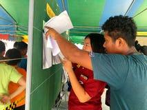 Povos tailandeses que verificam seus nomes na placa para eleger o governo novo após 6 anos de golpe longo no dia de pré-eleição o fotos de stock royalty free