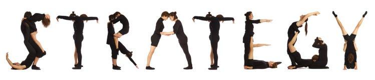 Povos vestidos preto que formam a palavra da ESTRATÉGIA Imagens de Stock
