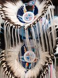 Pow Wow Headdress and Bustle with Feathers and Beaded Medallions. Close up of a feathered headdress and bustle with beaded medallions worn by a male fancy dancer stock photo