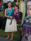 Pow-Wow Spectators. Anderson, California, USA-October 3, 2015:A mother and child view a large photo of a toddler dressed to perform at the Stillwater Pow-wow in stock photography