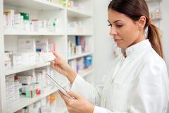 Poważna młoda żeńska farmaceuta bierze lekarstwa od półki fotografia royalty free