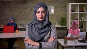 Poważna atrakcyjna arabska kobieta stoi będący ubranym hijab rossed i patrzejący kamerę z spokojną ufną pozycją