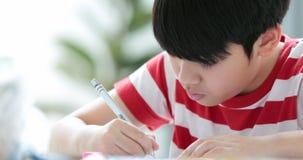 Poważna azjatykcia chłopiec robi twój pracie domowej w domu zdjęcie wideo