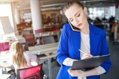 Poważna biznesowa kobieta pisze puszek informaci na pastylce Mówi z klientem obrazy royalty free