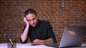 Poważna caucasian samiec w czarnym kostiumu rozważa i skupiał się na jego umysłach podczas gdy siedzący przy pracującym biurkiem