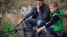 Poważna chłopiec łapie ryba z jego ojca brodatym brunet siedzi wpólnie i trzyma połowów prącia błonie zbiory