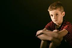 Poważna chłopiec Ściska jego kolana Przeciw Ciemnozielonemu Obrazy Stock