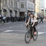 poważna dziewczyna krzyżuje drogę na bicyklu w błękitnej sukni z polek kropkami Zdjęcia Royalty Free
