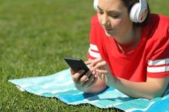 Poważna dziewczyna słucha muzyczna wyszukuje telefon zawartość na trawie obrazy stock